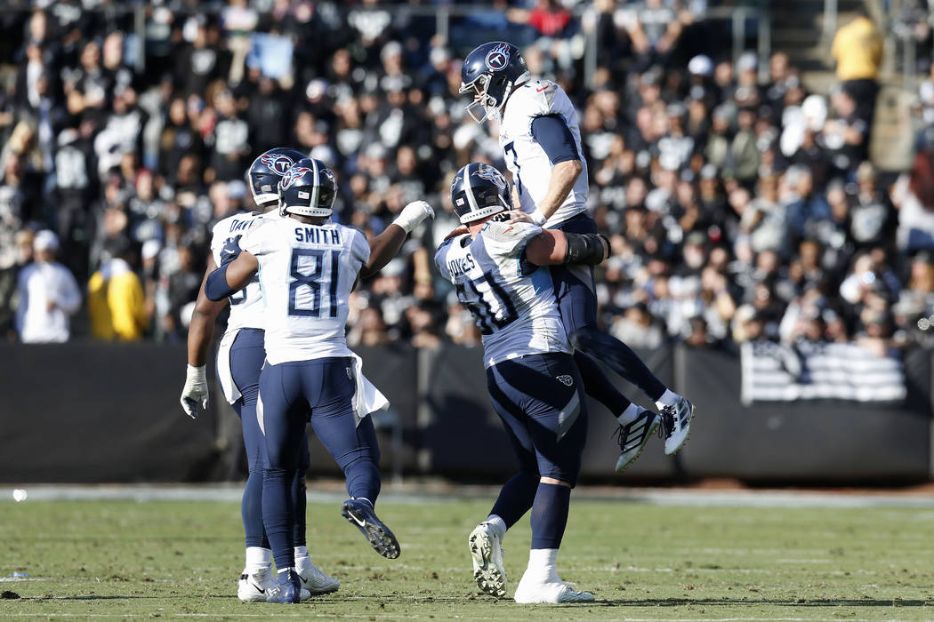 Tennessee Titans quarterback Ryan Tannehill, top, celebrates with teammates after throwing a to ...