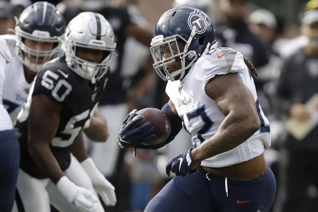 Tennessee Titans running back Derrick Henry, right, runs against the Oakland Raiders during the ...