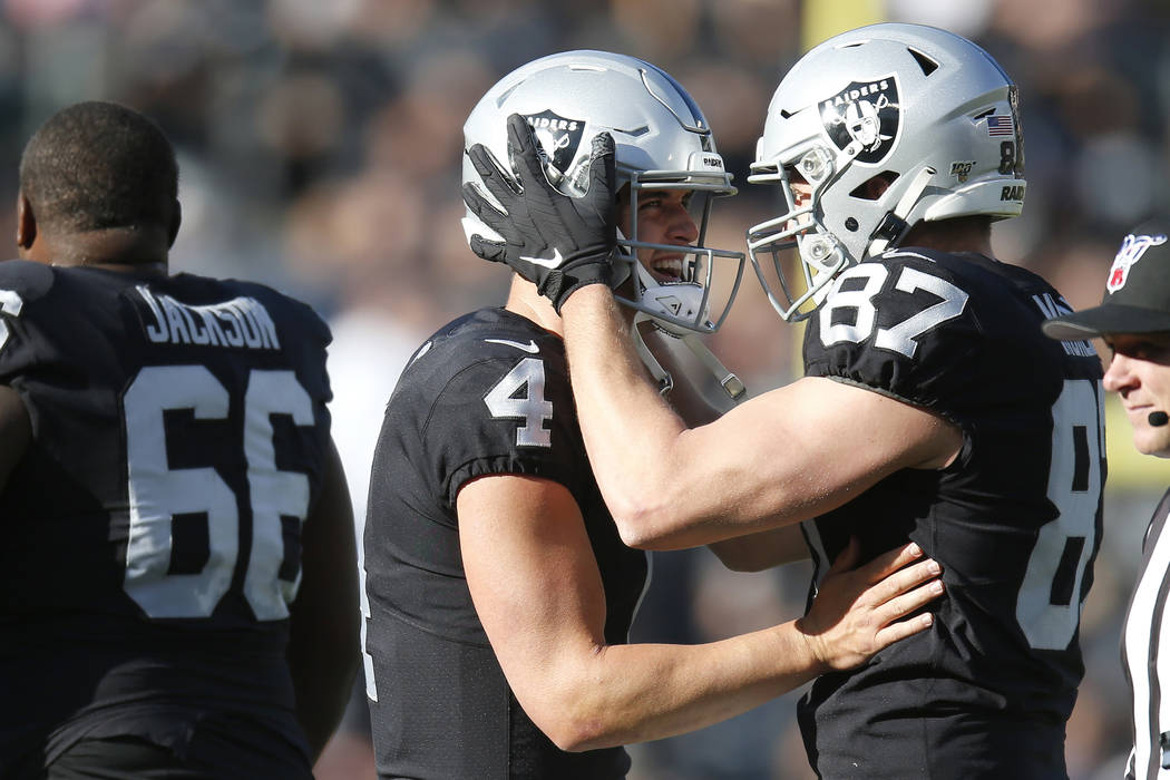 Oakland Raiders quarterback Derek Carr (4) celebrates with tight end Foster Moreau (87) after a ...