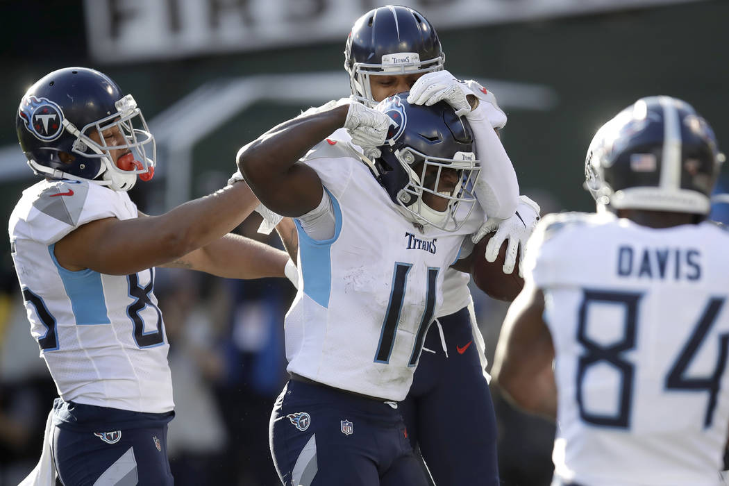 Tennessee Titans wide receiver A.J. Brown (11) is congratulated by teammates after scoring agai ...