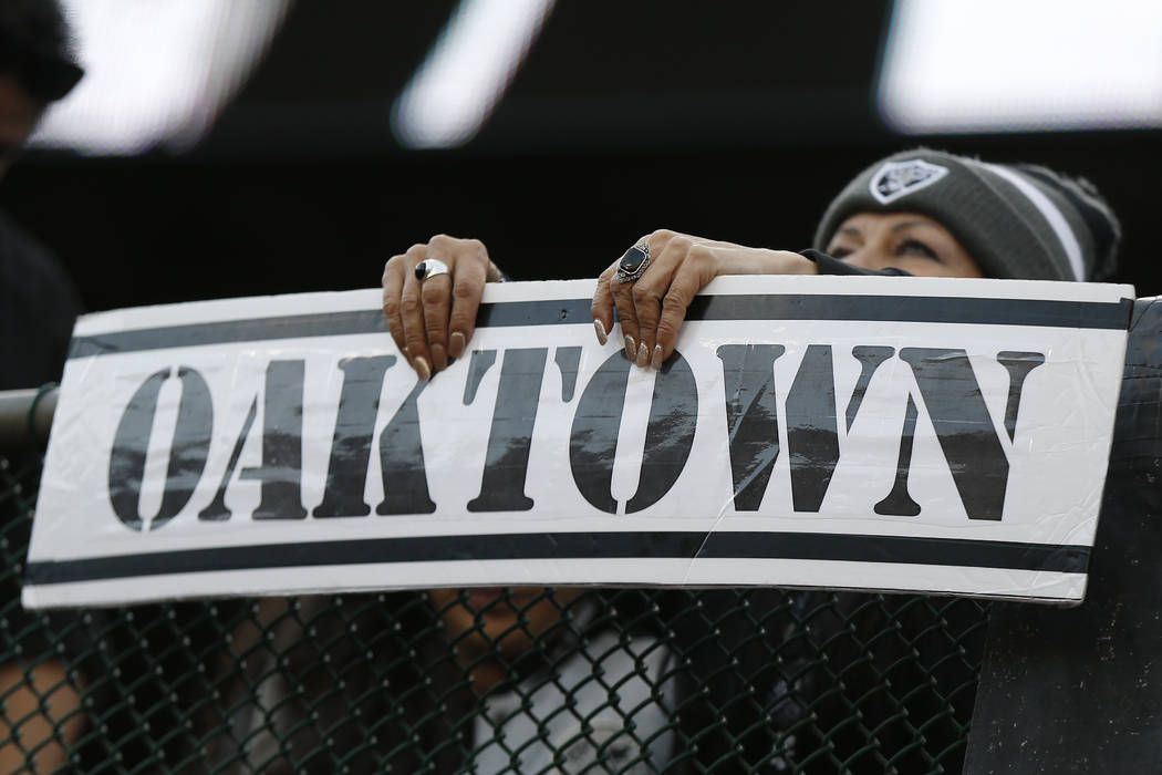 An Oakland Raiders fan holds up an Oaktown sign during the second half of an NFL football game ...