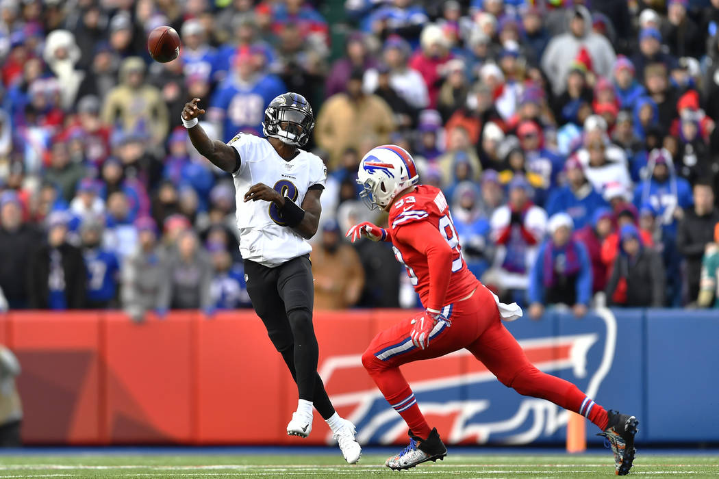 Baltimore Ravens quarterback Lamar Jackson (8) throws a pass under pressure by Buffalo Bills de ...