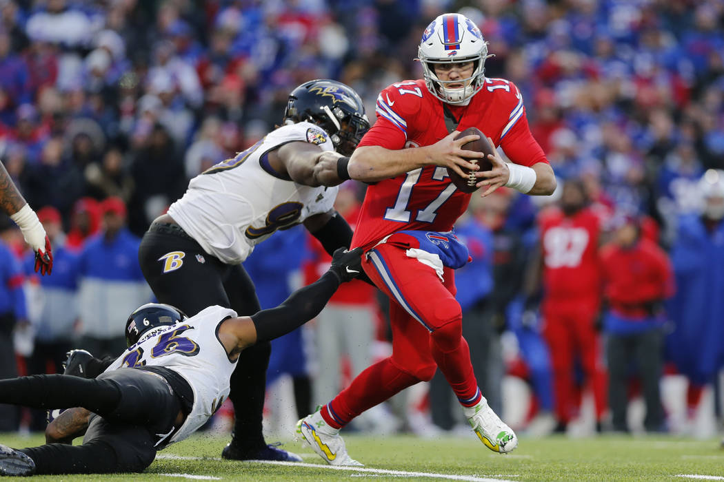 Buffalo Bills quarterback Josh Allen (17) is forced out of the pocket by Baltimore Ravens defen ...