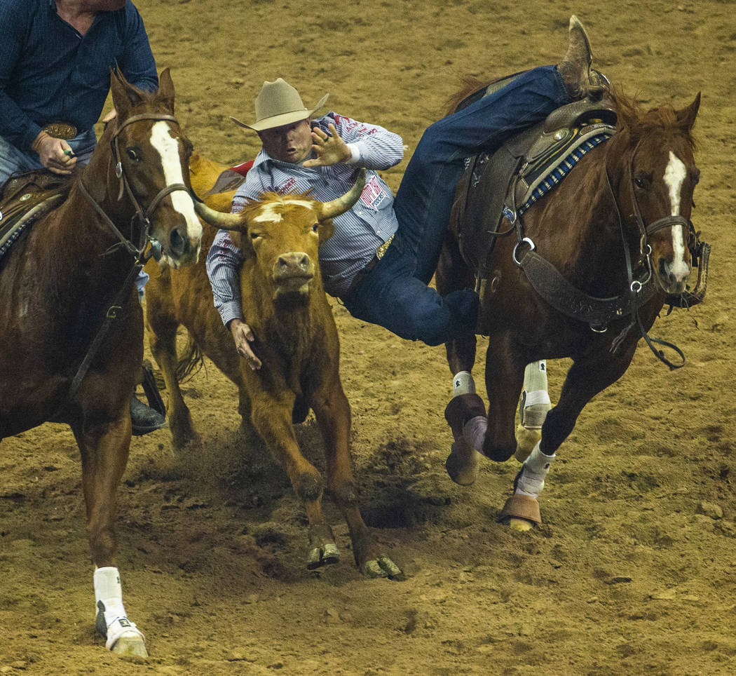 Hunter Cure of Holliday, Texas, leaps onto a steer in Steer Wrestling during the fourth go roun ...