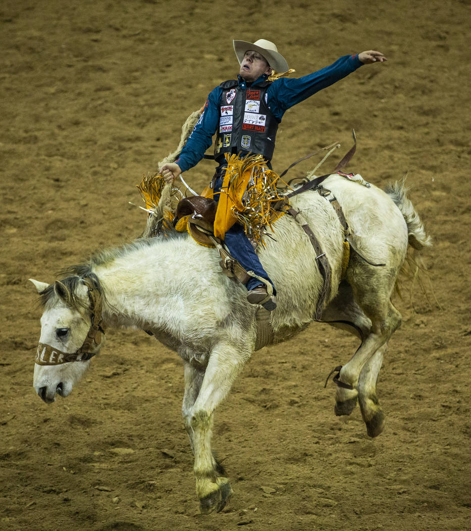 Brody Cress of Hillsdale, Wyo., catches some air atop Artificial Colors in Saddle Bronc Riding ...