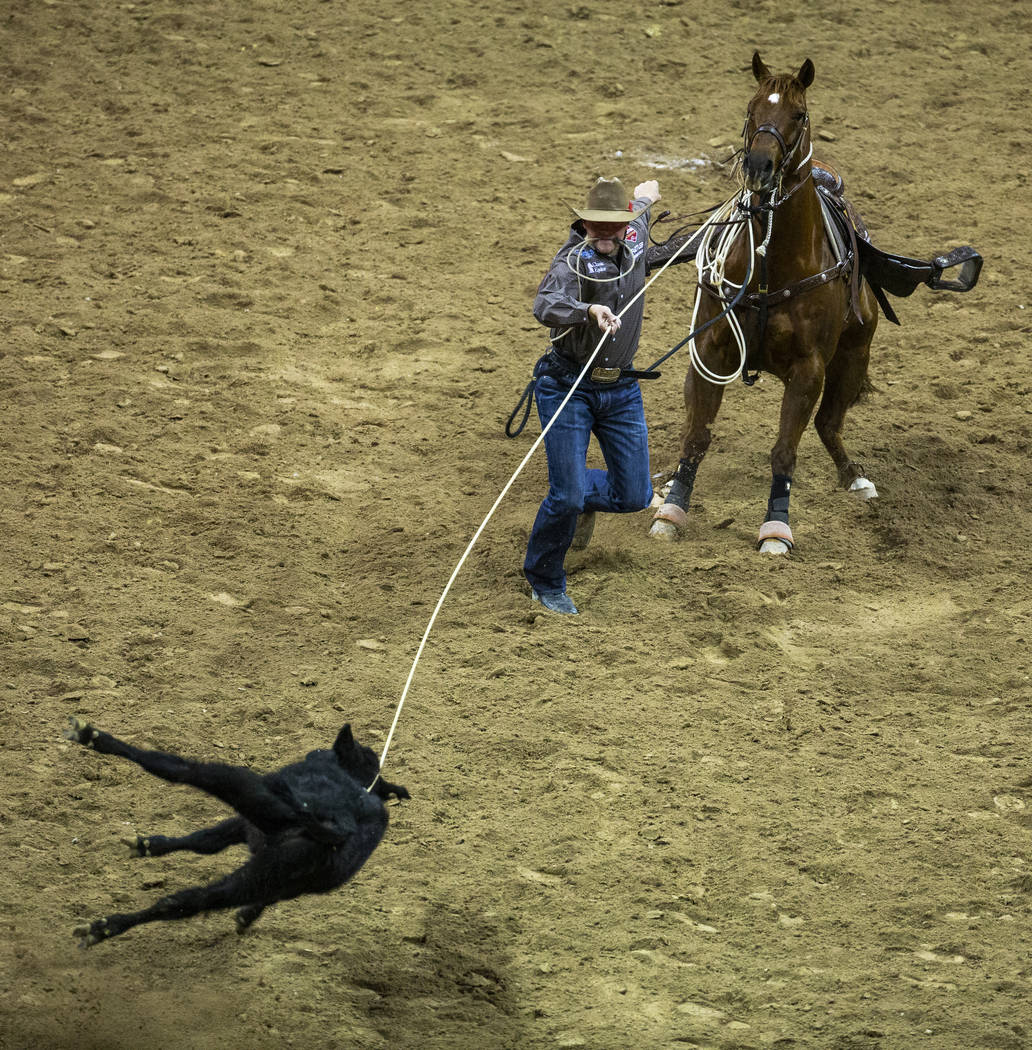 Cooper Martin of Alma, Kan., works to his calf in Tie-Down Roping during the fourth go round of ...