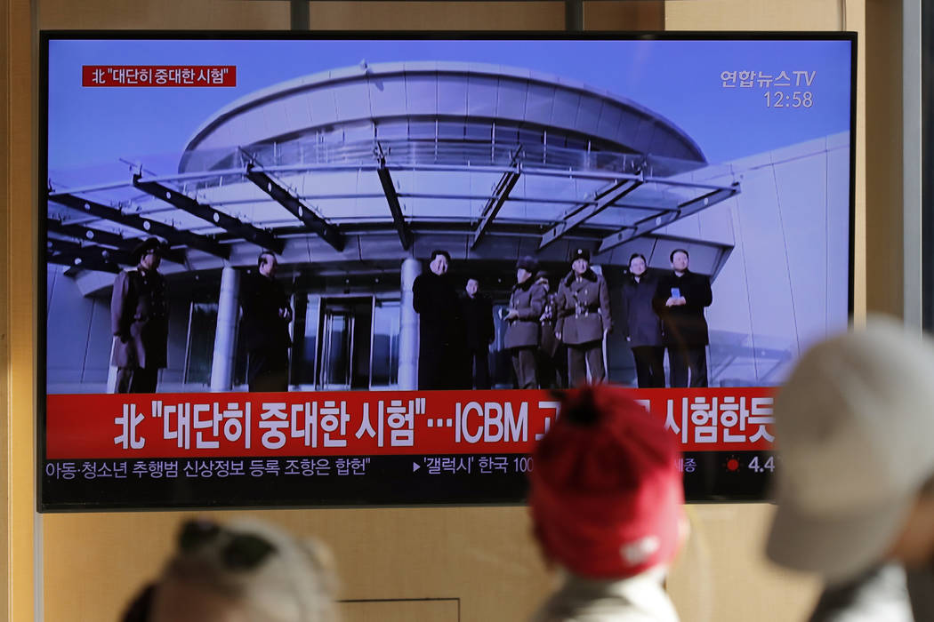 People watch a TV news program reporting North Korea's announcement with a file footage of Nort ...