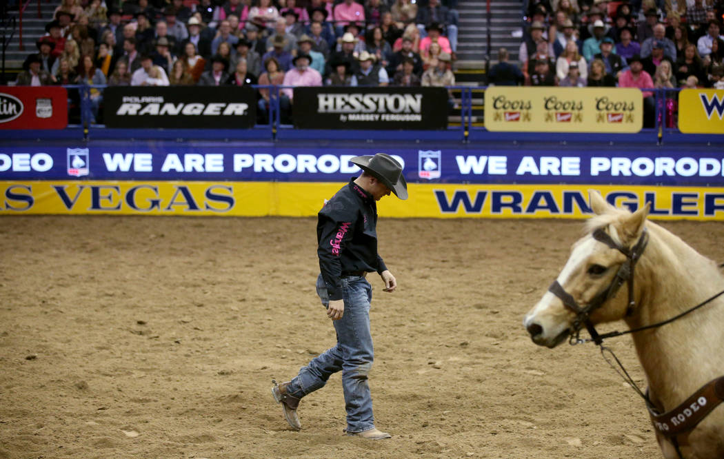 J.D. Struxness of Milan, Minn. walks off the dirt after failing to catch his steer in the Steer ...
