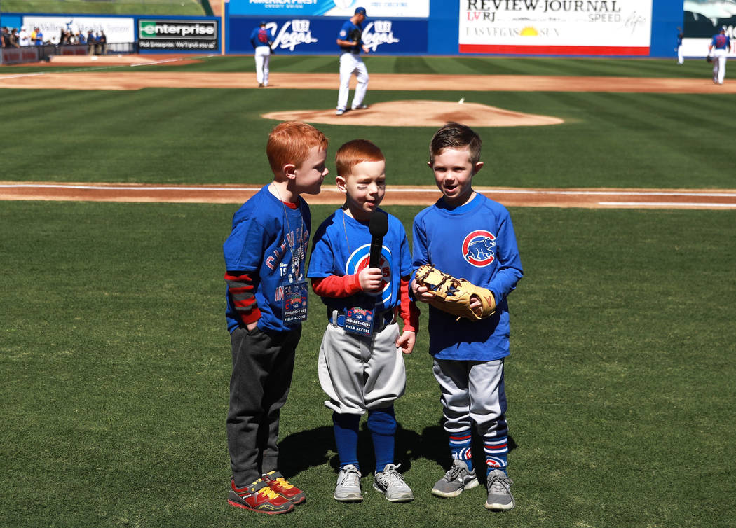 Three young boys announce the start of the annual Big League Weekend baseball game at Cashman F ...