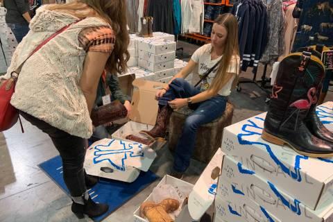 Caela Garland, right, of Nampa, Idaho, tries on a pair of cowboy boots as mom Rhonda Garland of ...
