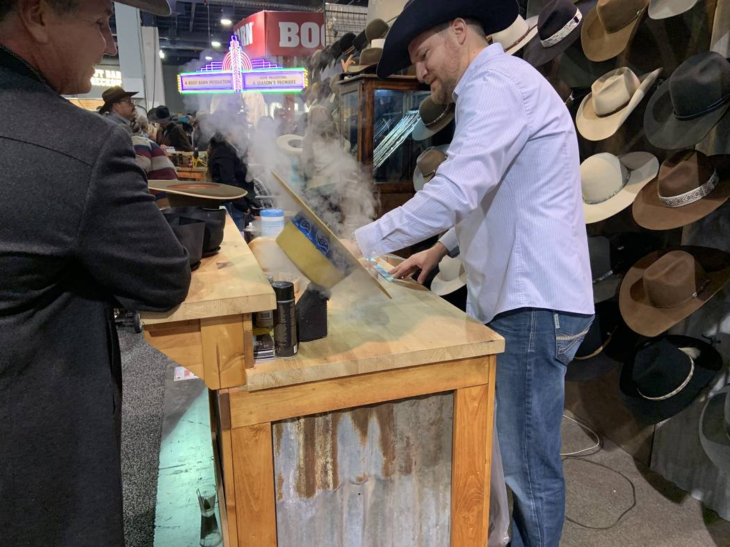 Custom hat maker Braydan Shaw plies his trade as customer Mitch Clum looks on Saturday at the B ...