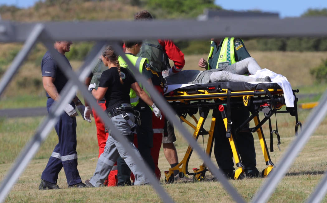 Emergency services attend to an injured person arriving at the Whakatane Airfield after the vol ...