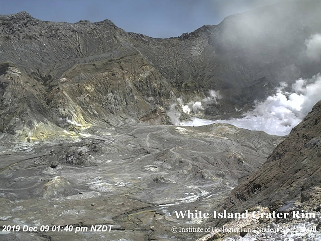 In this image released by GeoNet, tourists can be seen near the volcano's crater Monday, Dec. 9 ...