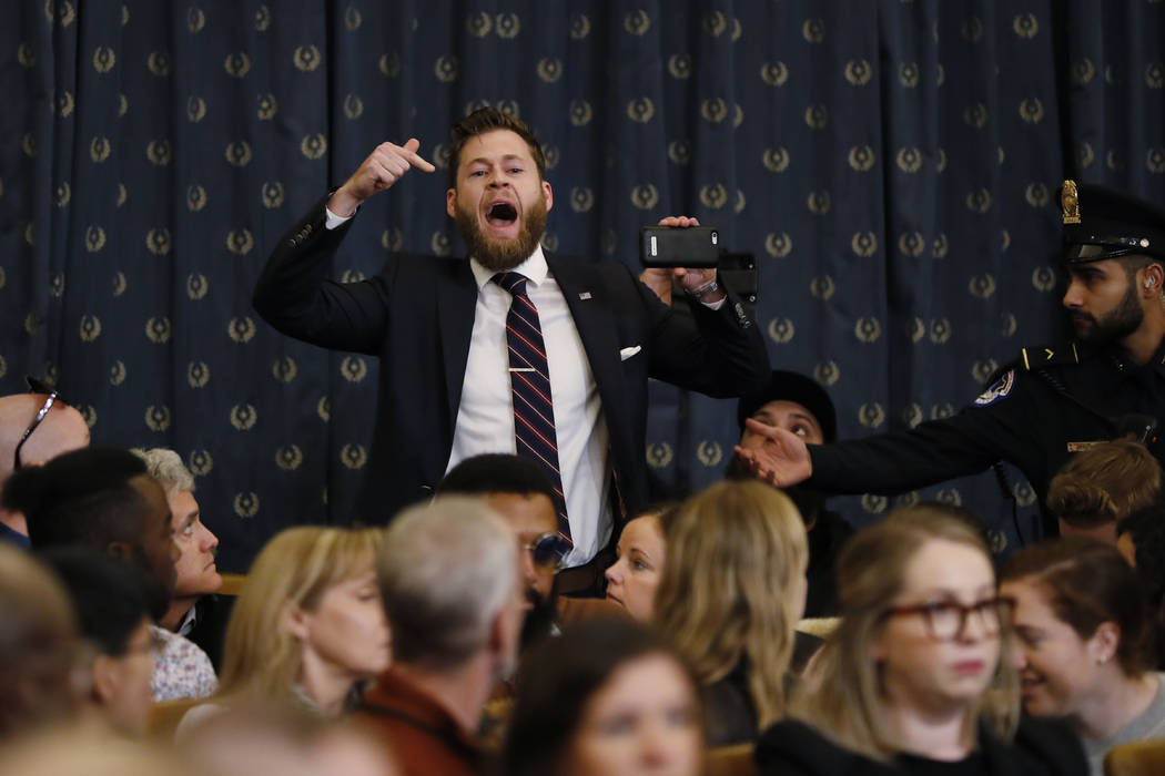 A protestor speaks out as the House Judiciary Committee hears investigative findings in the imp ...