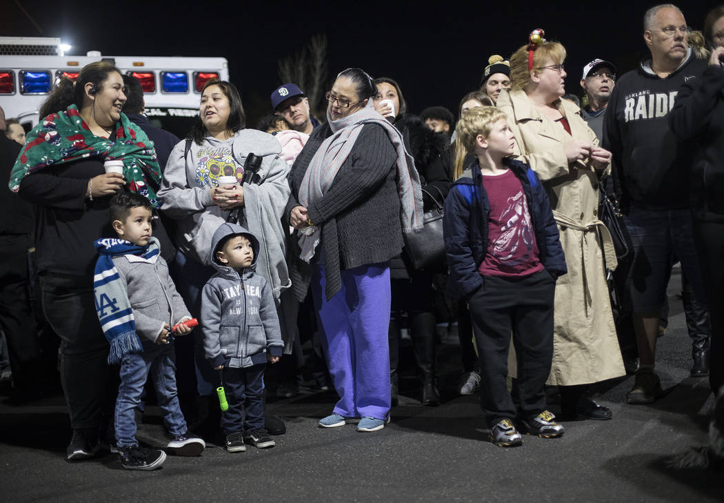 A crowd waits in the parking lot to shine flashlights at children who are stuck in the hospital ...