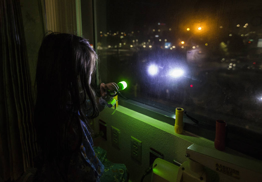 Alicia Langoria-Buffington, 5, shines a flashlight back at a crowd of people in the parking lot ...