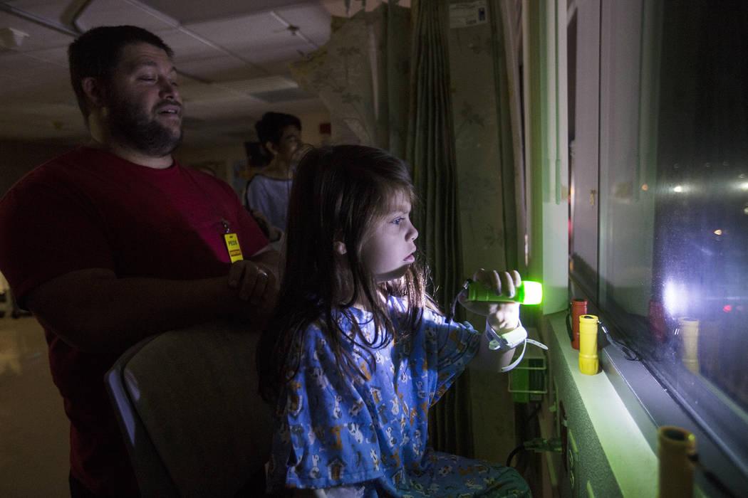 Alicia Langoria-Buffington, 5, in front of her dad David Langoria-Buffington, shines a flashlig ...