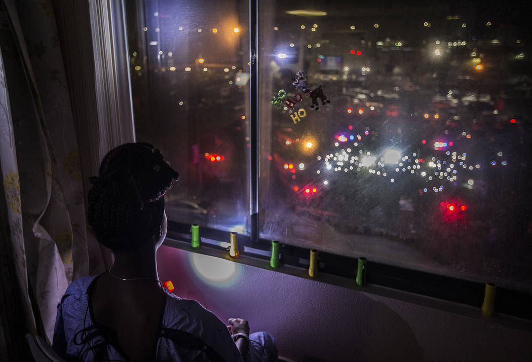 Zion Green, 12, shines a flashlight back at a crowd of people in the parking lot flashing light ...
