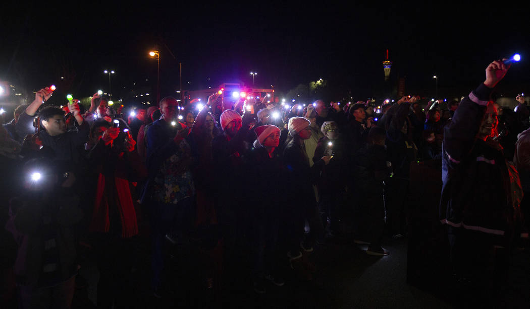 A group of community members and first responders shine lights into the third floor of UMC Chil ...