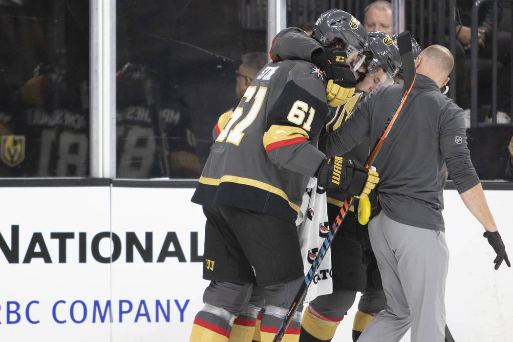 Golden Knights center Cody Glass (9) is carried off the ice by teammates Mark Stone (61) and Jo ...