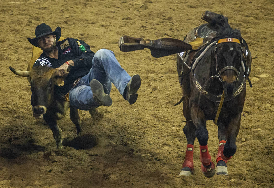 Bridger Chambers of Stevensville, Mont., leaps onto a steer for a time of 3.60 seconds and firs ...
