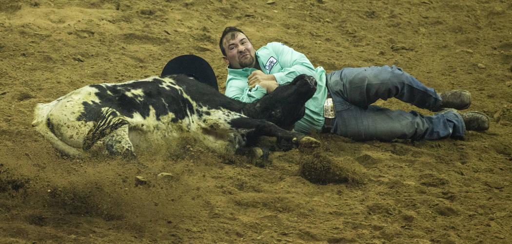 Tanner Brunner of Ramona, Kan., gets down in the dirt for Steer Wrestling during the fourth go ...