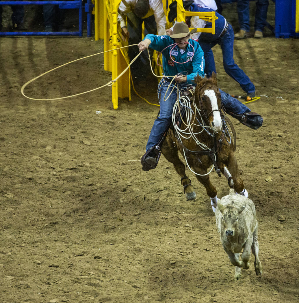 Tuf Cooper of Decatur, Texas, bears down on his calf in Tie-Down Roping during the fourth go ro ...