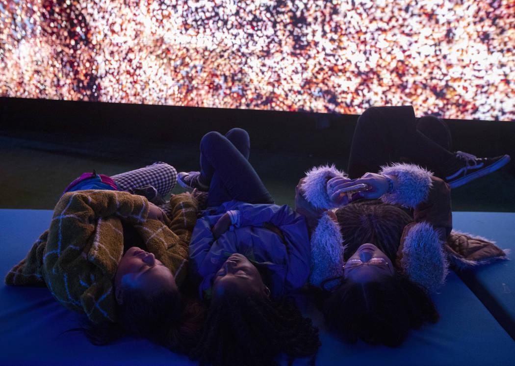 Tanisha Tavares, left, Raina Brown, center, and Jennifer Paloma, right, take a rest while watch ...