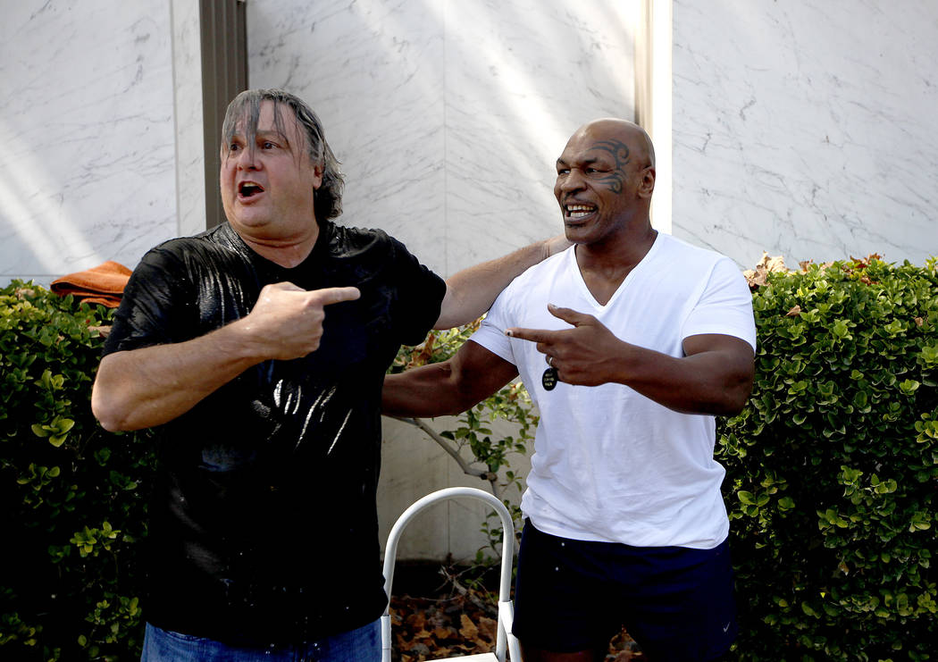 Mike Tyson laughs moments after dumping ice water on Las Vegas attorney David Chesnoff, left, o ...