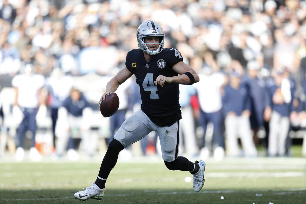 Oakland Raiders quarterback Derek Carr (4) rolls out to pass against the Tennessee Titans durin ...