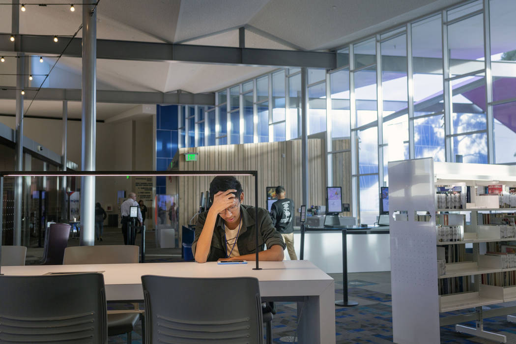 John Ollado, 20, watches a video on his phone at the East Las Vegas Library in Las Vegas on Tue ...