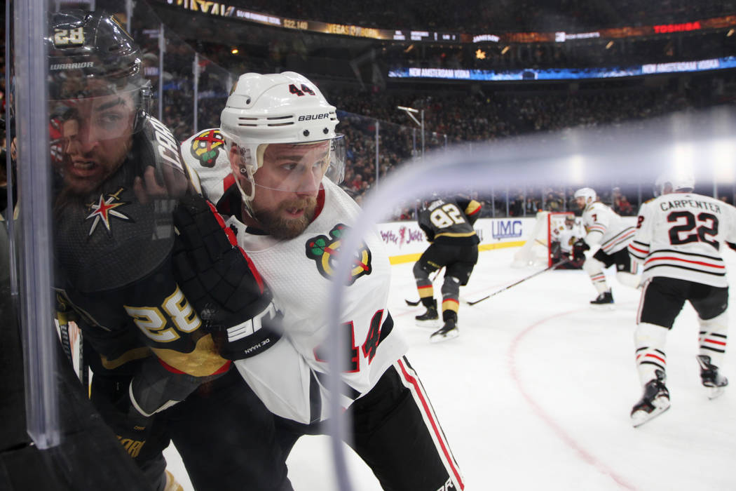 Vegas Golden Knights left wing William Carrier (28) is slammed against the glass by Chicago Bla ...