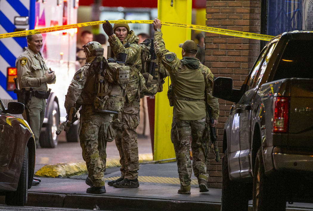 SWAT officers with Las Vegas police arrive in the parking lot as they work a barricade situatio ...