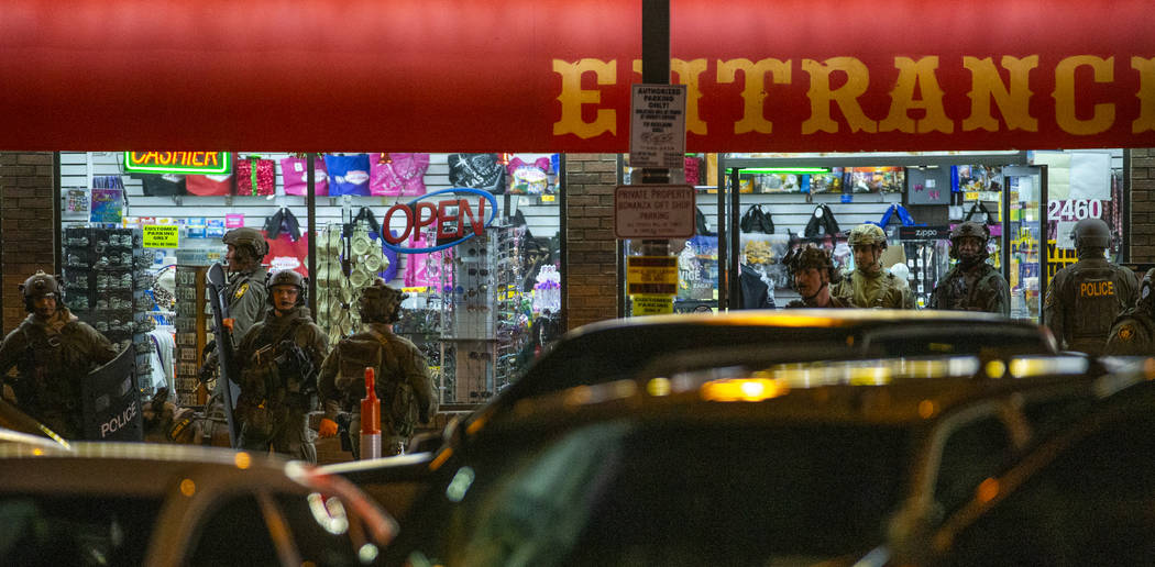 Las Vegas police gather at the store entrance as they work a barricade situation of a woman wit ...