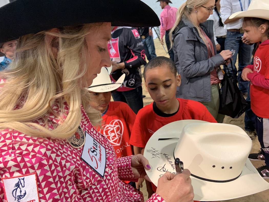 Wrangler NFR barrel racer Amberleigh Moore pens her autograph on a cowboy hat for one of the sp ...
