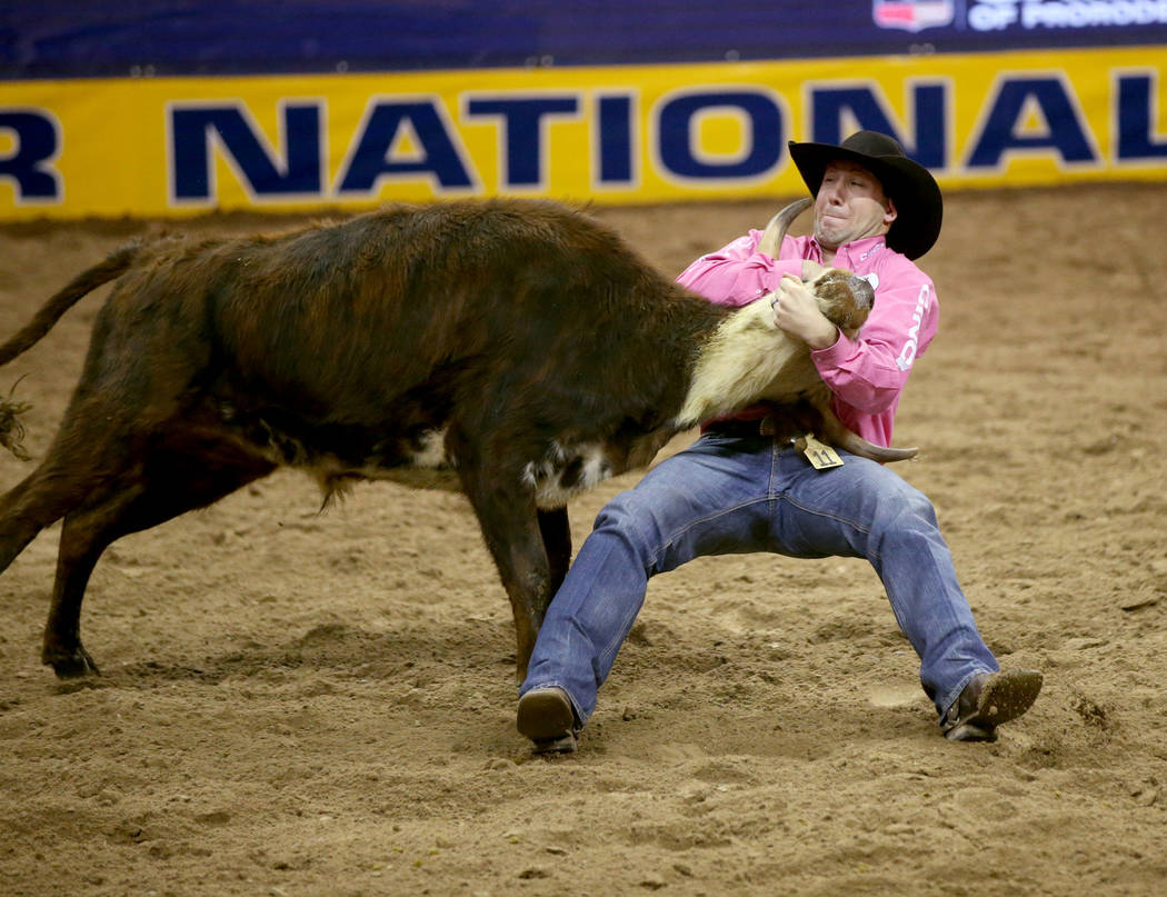 Scott Guenthner of Canada competes in Steer Wrestling during Bareback Riding in the fifth go-ar ...