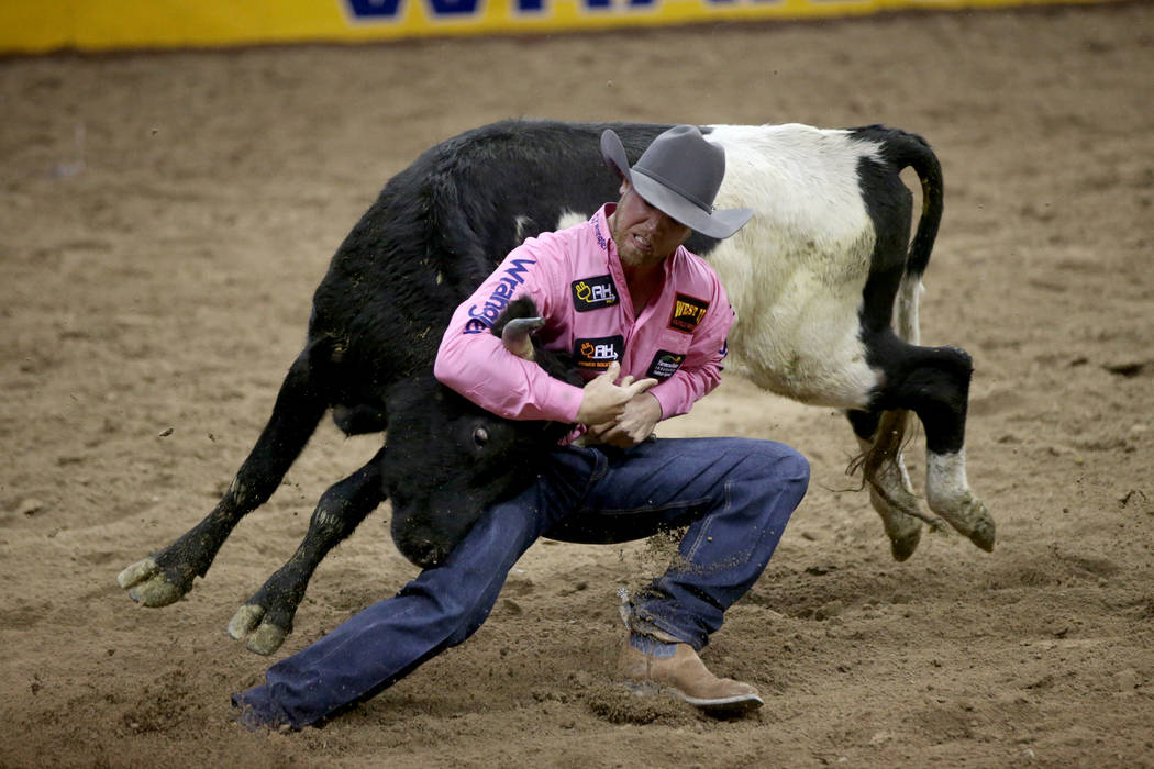 Cameron Morman of Glen Ullin, N.D. competes in Steer Wrestling during Bareback Riding in the fi ...