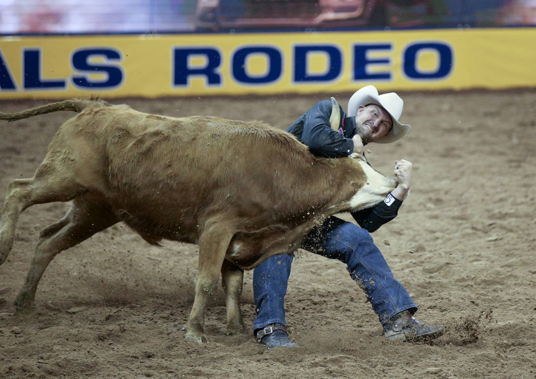 Kyle Irwin of Robertsdale, Ala. competes in Steer Wrestling during Bareback Riding in the fifth ...