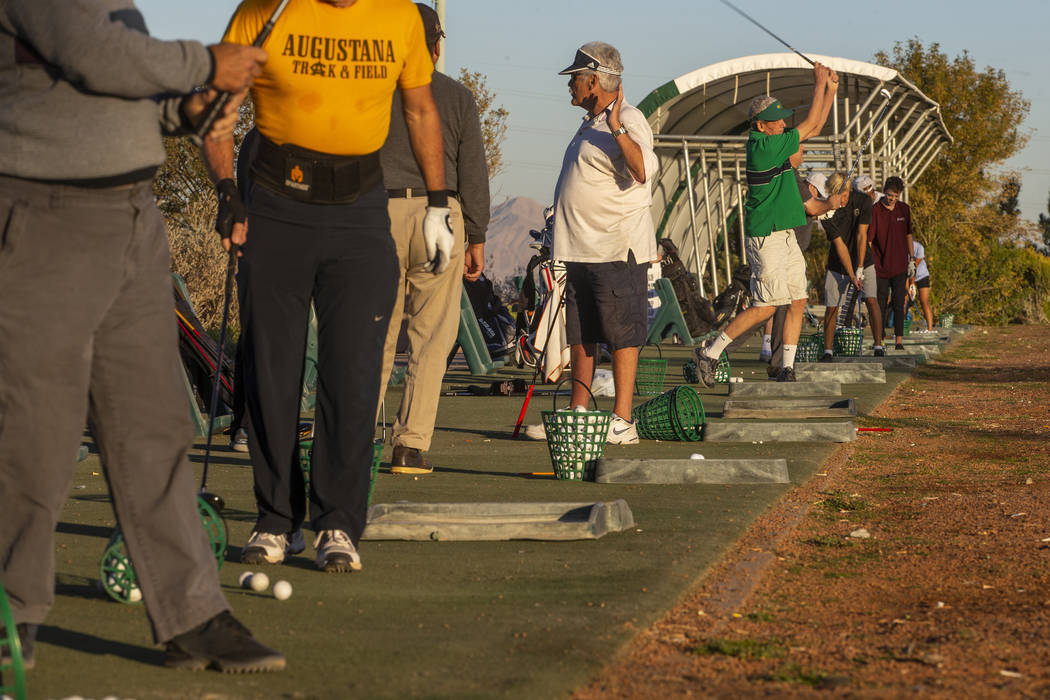 Golfers practice on the driving range near the clubhouse on the Palm Course at the Angel Park G ...