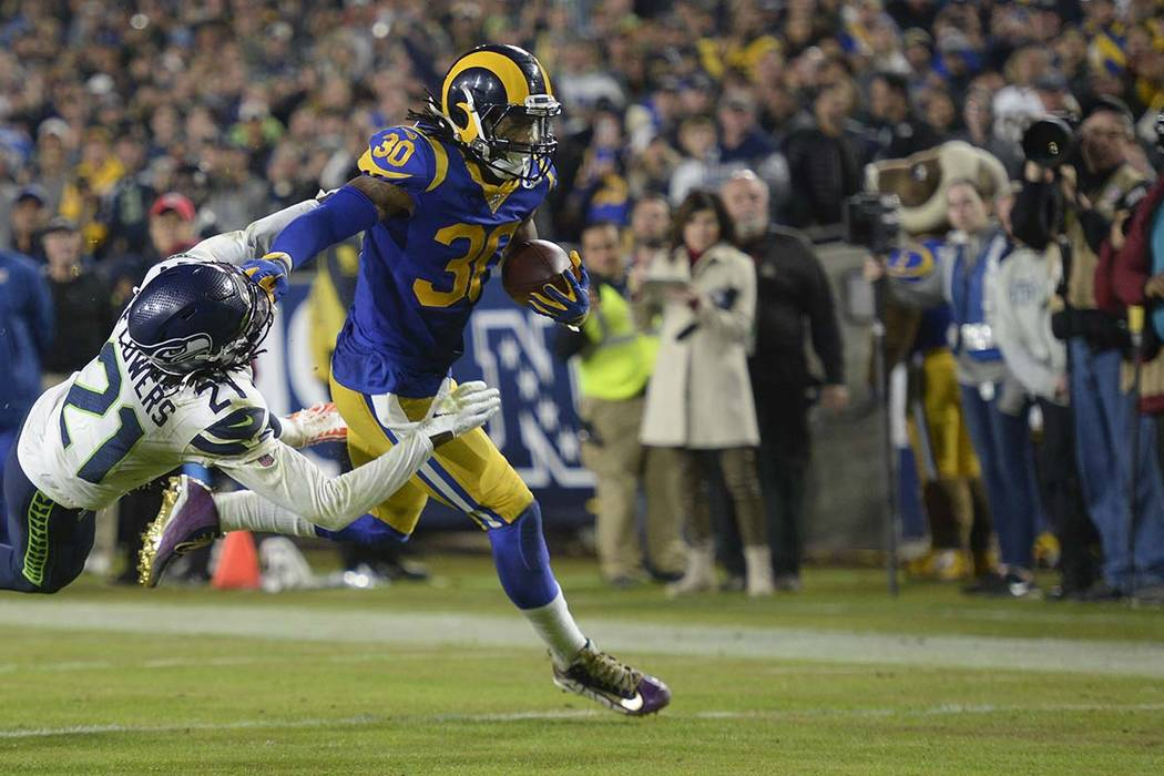 Los Angeles Rams running back Todd Gurley, right, stiff arms Seattle Seahawks cornerback Tre Fl ...