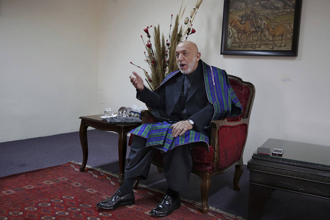 Former Afghan President Hamid Karzai gestures while speaking during an interview with The Assoc ...