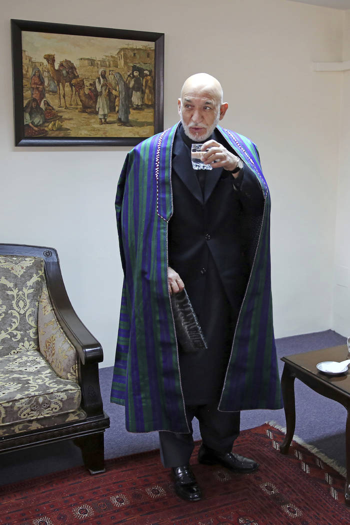 Former Afghan President Hamid Karzai drinks a glass of water after an interview with The Associ ...
