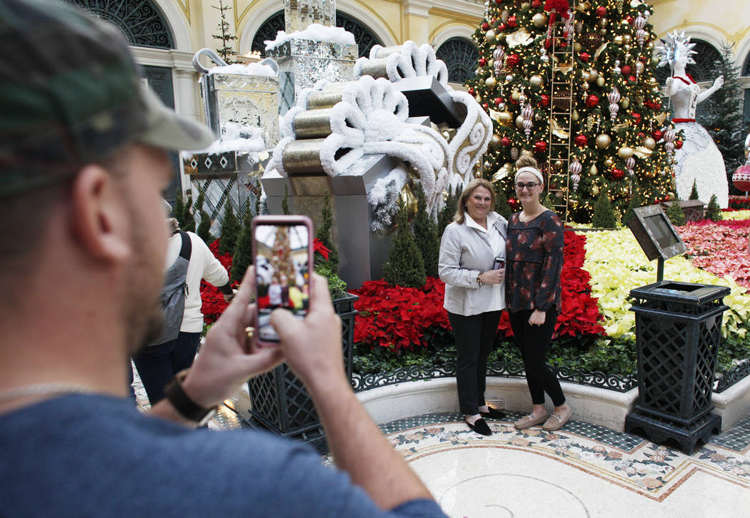 Rick Musser takes a photo of Carol Vallozzi, left, and his wife Hannah Musser at the Bellagio C ...