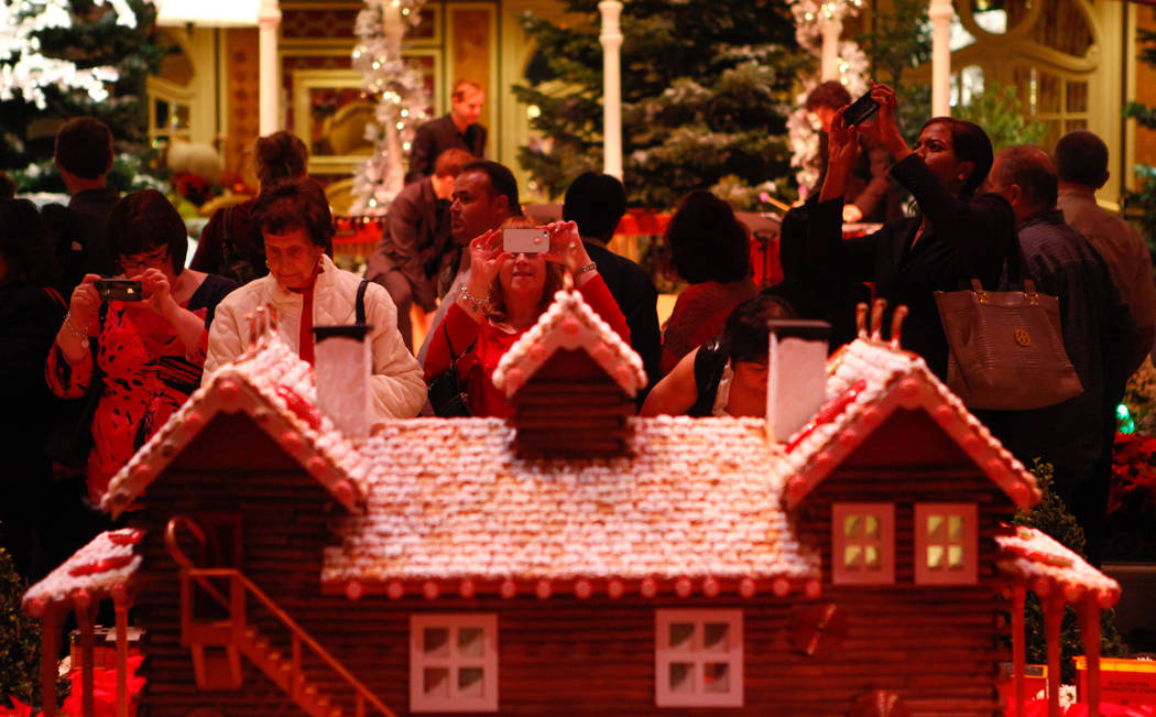 People take pictures of a miniature Christmas village after the Christmas tree lighting at the ...