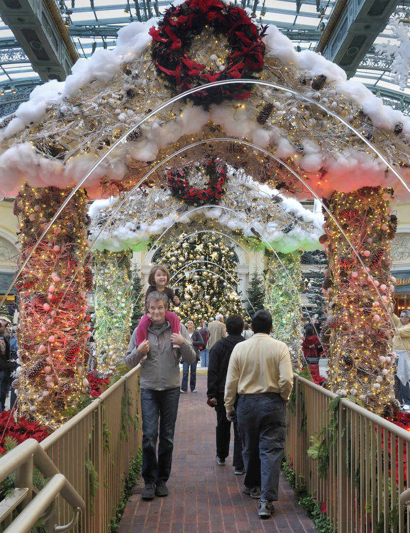 Las Vegas resident Robert Kilpatrick and his 3-year-old daughter, Marley, pass under decorated ...