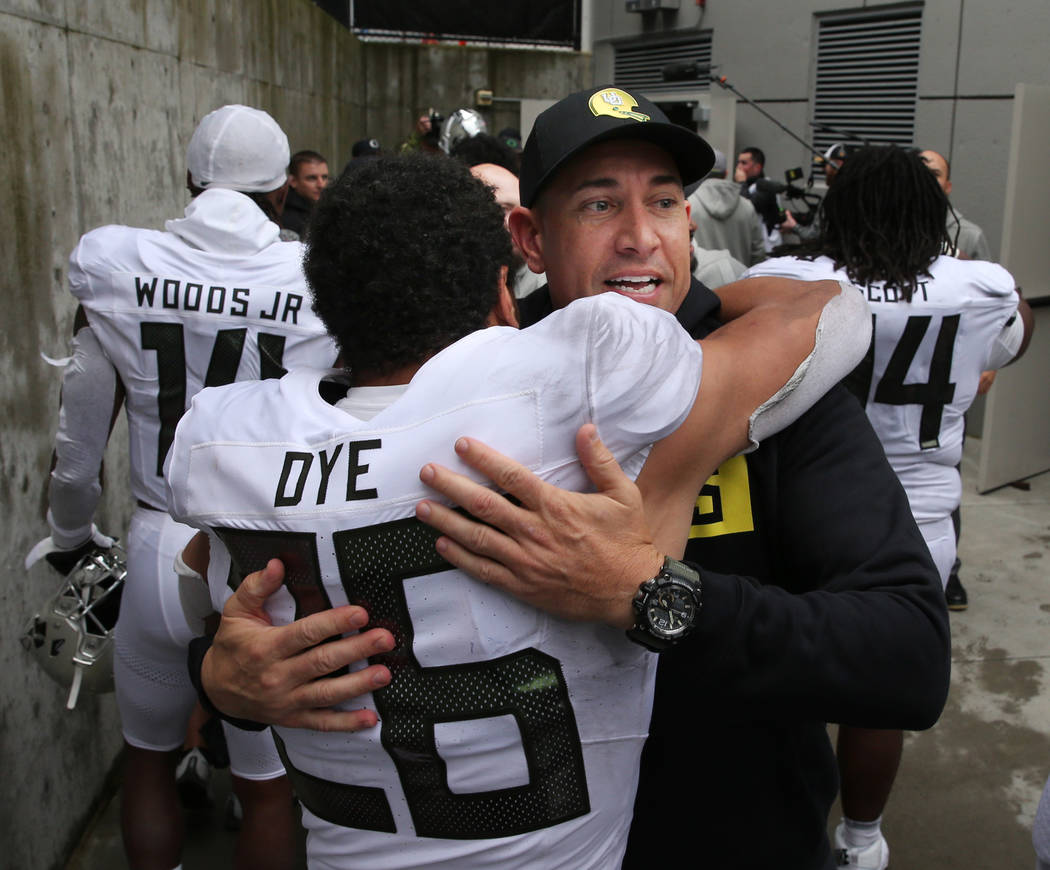 Oregon offensive coach Marcus Arroyo celebrates with Travis Dye after the win over Washington o ...