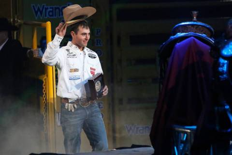 Clay Smith of Broken Bow, Okla. (22) walks up to be honored on stage after winning the Team Rop ...