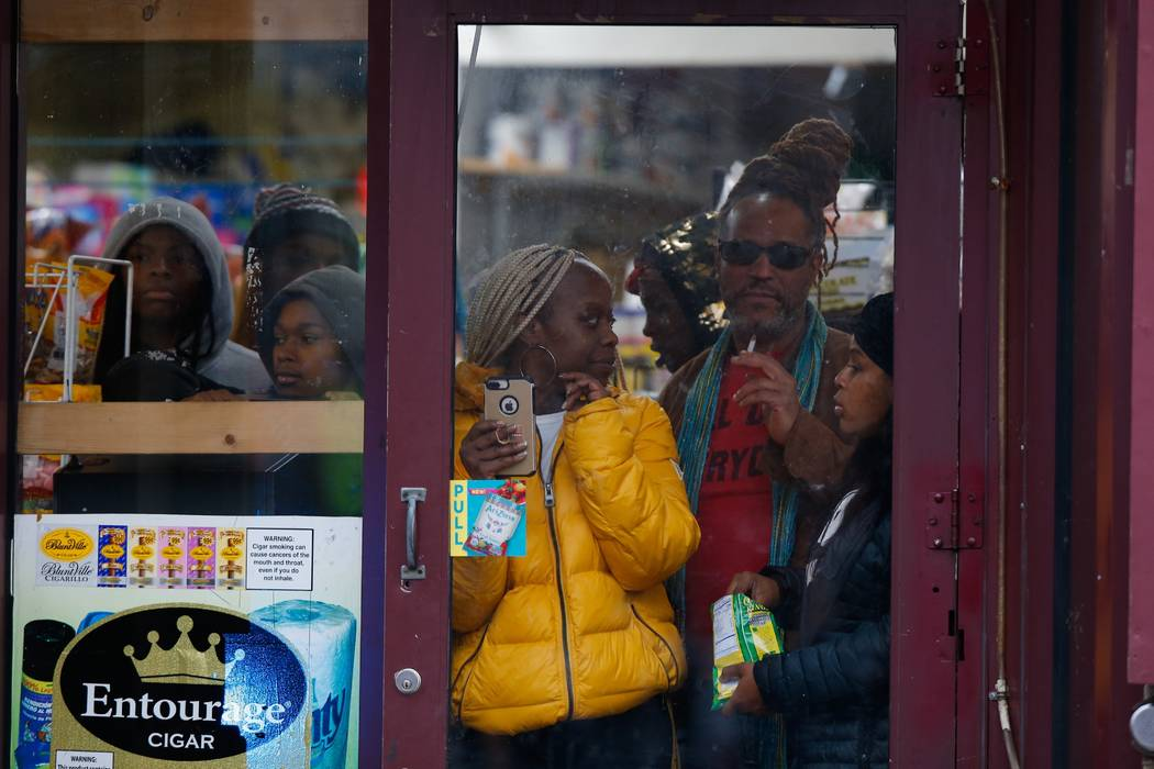 Bystanders look out from a store as law enforcement arrives at the scene following reports of g ...