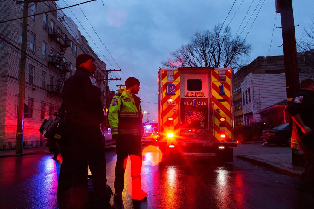 First responders and law enforcement personnel stand near the scene following a shooting, Tuesd ...