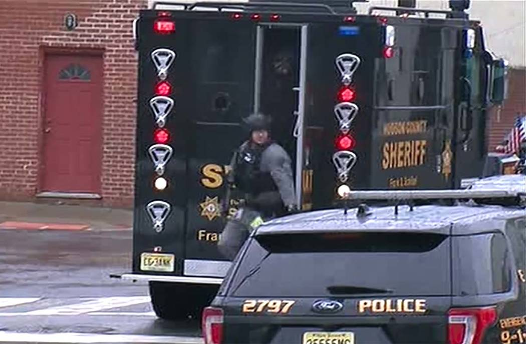 In an image taken from video, Hudson County Swat team officers arrive at the scene following re ...